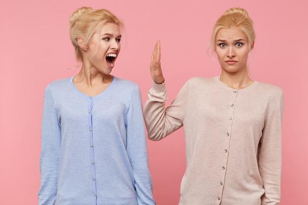 Tijdens een conflict tussen de tweeling weigert een van de zussen te luisteren naar de kreet van een ander geïsoleerd op een roze achtergrond.
