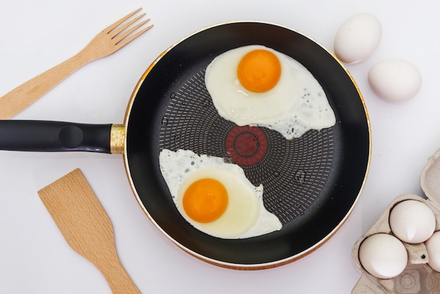 Tijdens het bereiden van ontbijt met verse eieren. gebakken eieren van twee eieren in een koekenpan.