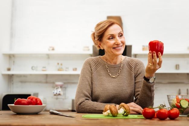 Tijdens het kookproces. tevreden lichtharige vrouw met brede glimlach die mooi op peper in haar hand kijkt