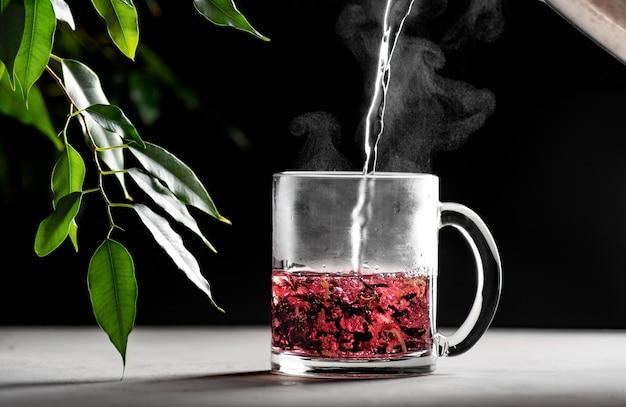 Tijdens het maken van rode thee wordt kokend water in een transparante mok op een donkere achtergrond gegoten