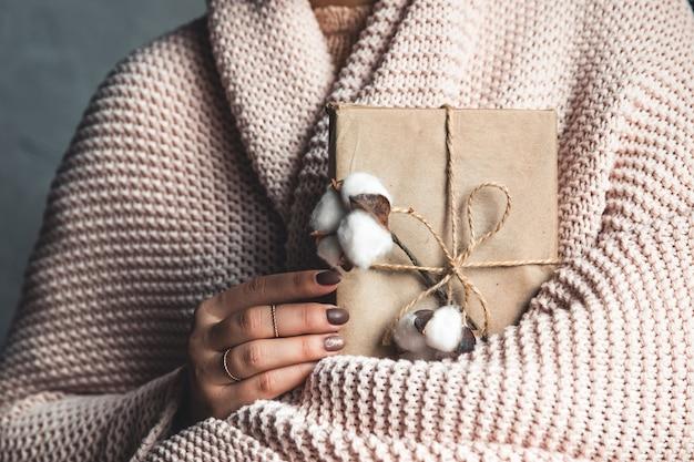 Tijdgeschenken - geschenkdoos in handmeisjes. geschenk in de handen van een vrouw. plaid, katoen, manicure. valentijnsdag