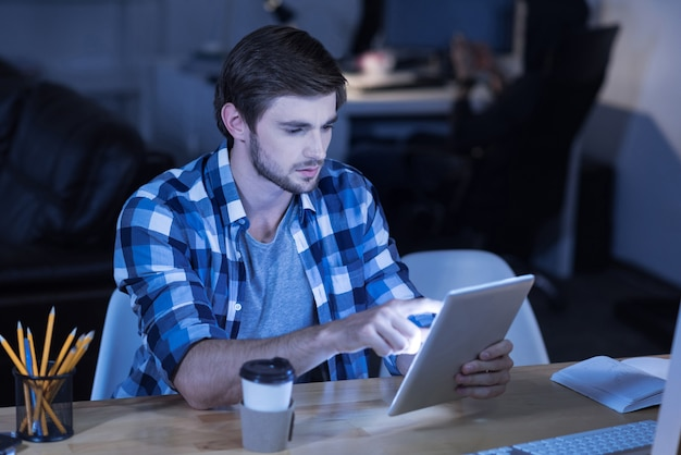 Tijdperk van technologie. knappe jonge bebaarde man zittend aan tafel en het gebruik van tablet terwijl het drinken van koffie