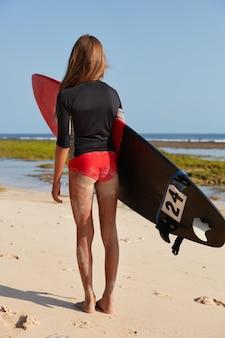 Tijdverdrijf en sport concept. verticale opname van gezonde slanke dame heeft zand op benen, bereidt zich voor op professioneel surfen
