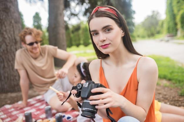 Tijdverdrijf, picknick. schattig langharig meisje in heldere tshirt met camera in handen en vrienden achter chatten in de natuur