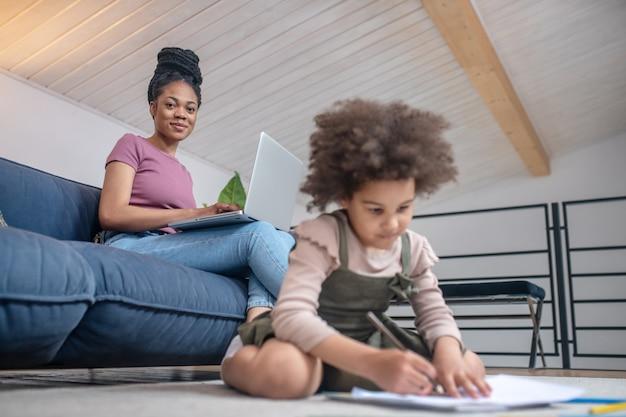 Tijdverdrijf thuis. glimlachende jonge mooie donkere vrouw met laptop op de bank en klein meisje zittend op de vloer tekenen met potloden