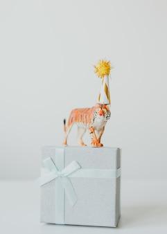 Tijgerbeeldje in feestmuts op een geschenkdoos symbool van chinees nieuwjaar 2022
