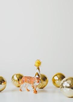 Tijgerbeeldje in feestmuts op witte achtergrond met gouden kerstballen