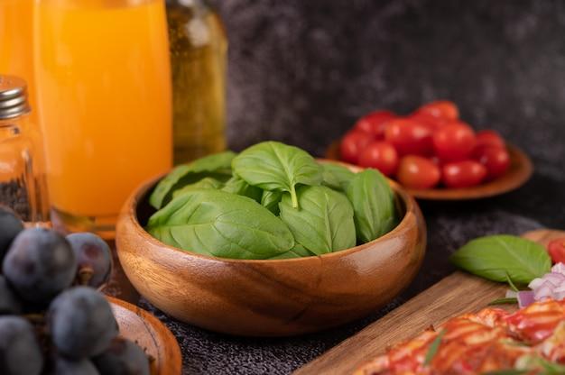 Tijm en tomaten in een houten beker met knoflook op een houten snijplank.