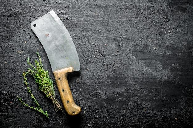 Tijm met een groot mes. op zwarte rustiek