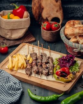 Tikka kebab geserveerd met frietjes en groene salade
