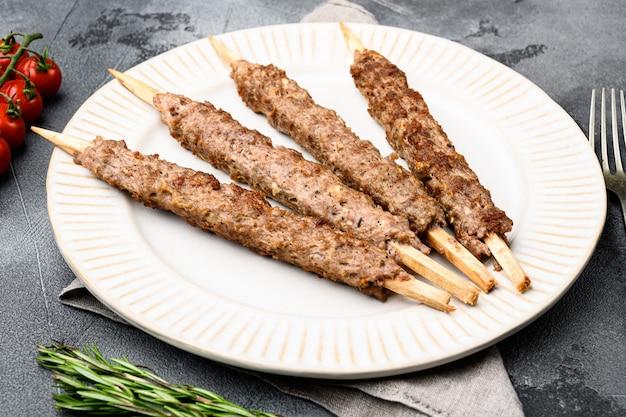 Tikka, shish en kofta kebab set, op plaat, op grijze stenen tafel achtergrond