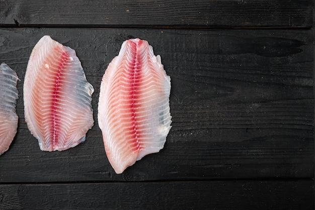 Tilapia-vis, vlees zonder vel, op zwarte houten tafel, bovenaanzicht met kopieerruimte voor tekst