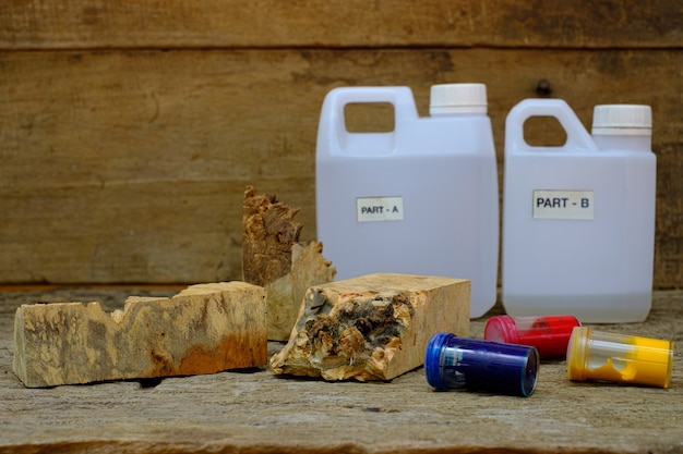 Timber burl houtsnippers kleur fles en hars epoxy voor het gieten van hout op oude houten tafel achtergrond