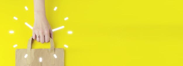 Time management duur interval grafisch concept. gerecycleerde bruine papieren boodschappentas in de hand met hologram klokpictogram op gele achtergrond, plat gelegd. zomer verkoop concept. levering dienstverleningsconcept.