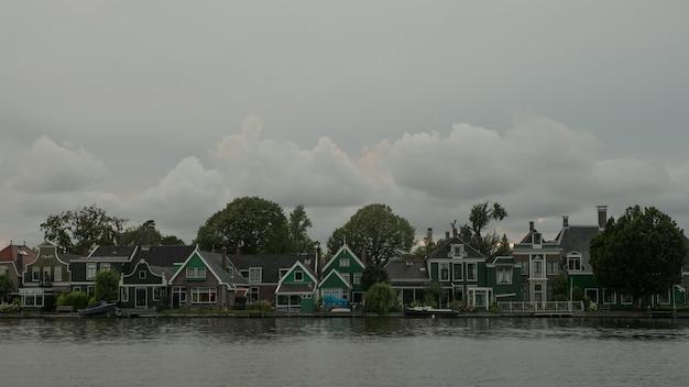 Timelapse van wolken boven huizen aan rivieroever nederland