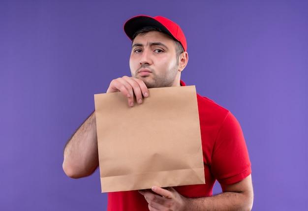 Timide jonge bezorger in rood uniform en pet met papieren pakket verward staande over paarse muur