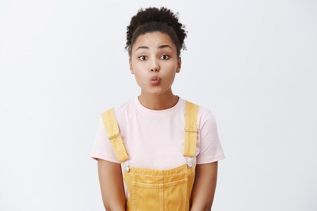 Timide vrouw wacht zenuwachtig op eerste kus, staand in schattige gele tuinbroek over t-shirt, lippen vouwend om mwah te geven, teder en vrouwelijk poseren over grijze muur