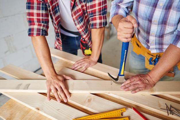 Timmerlieden die spijkers uit hout verwijderen
