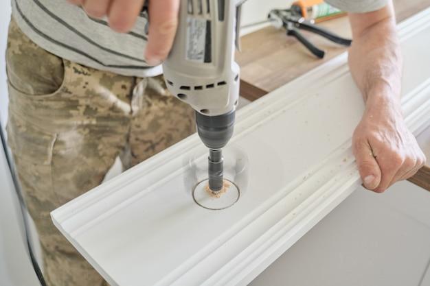 Timmerlieden hand met behulp van professionele houtbewerking elektrisch gereedschap