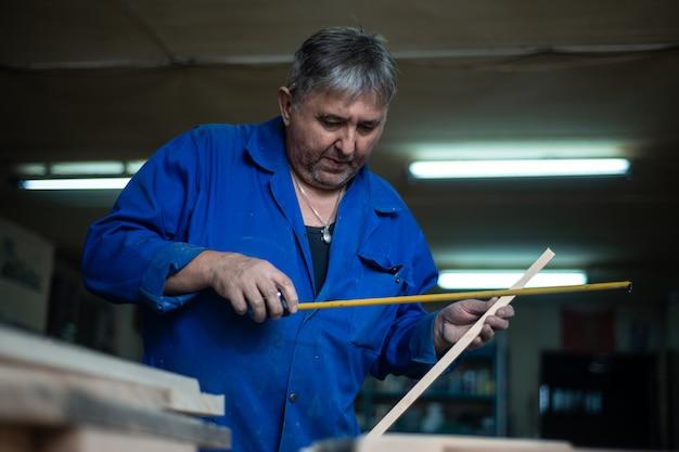 Timmerman aan het werk in de werkplaats, een man doet metingen