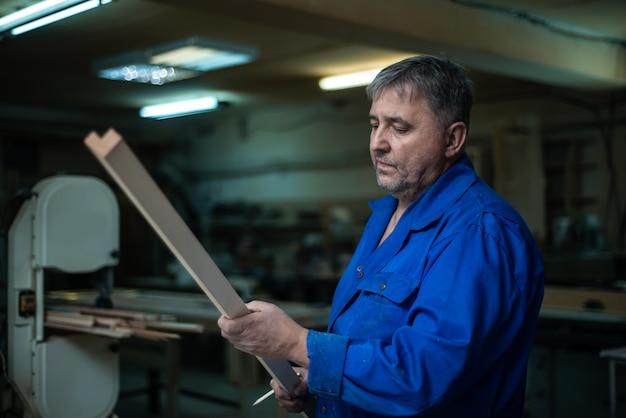 Timmerman aan het werk in zijn atelier, houtverwerking op een houtbewerkingsmachine