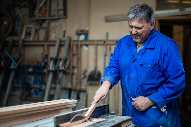Timmerman aan het werk in zijn atelier, houtverwerking