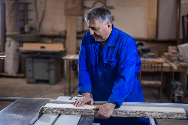 Timmerman aan het werk in zijn werkplaats, houtverwerking op een houtbewerkingsmachine
