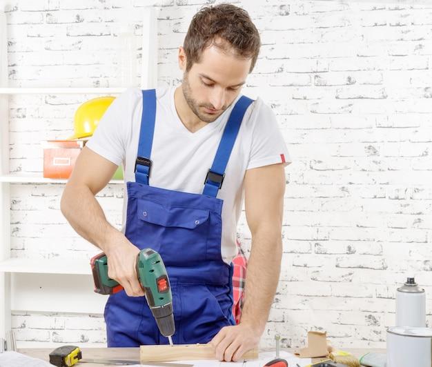 Timmerman boren gat in plank, in zijn atelier