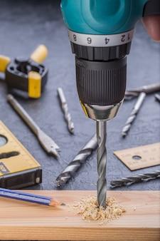 Timmerman boren hout met behulp van draagbare boormachine