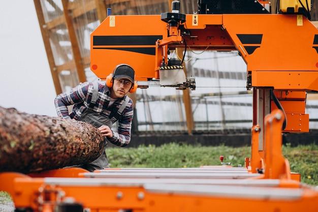 Timmerman die aan een zagerij aan een houten vervaardiging werkt
