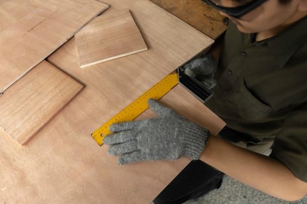Timmerman die aan houtbewerkingsmachines werken in timmerwerkwinkel. deskundige timmerman die een stuk hout in zijn houtbewerkingsworkshop snijdt.