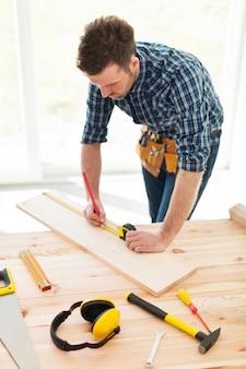 Timmerman die afmetingen van houten plank controleert