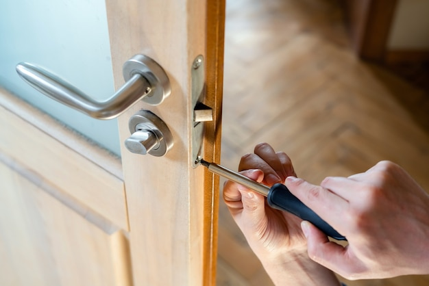 Timmerman die deurslot herstelt. een deurklink installeren
