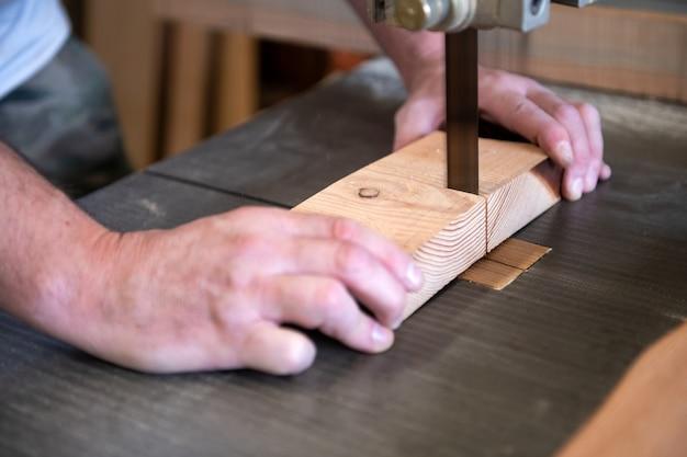 Timmerman die een blok hout op een lintzaag snijdt