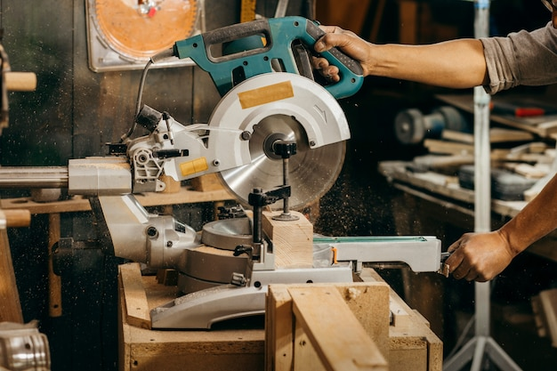 Timmerman die een cirkelzaag gebruikt om de lengte van houtnoppen in te korten.