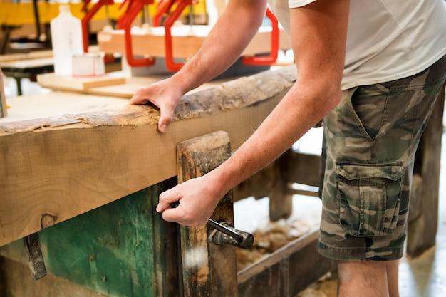 Timmerman die een houten plank in een ondeugd aanhalen