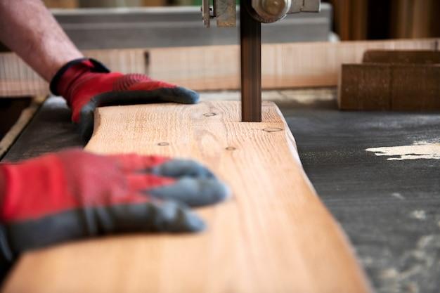 Timmerman die een houten plank met een lintzaag snijdt