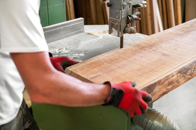 Timmerman die een houten plank op een lintzaag snijdt