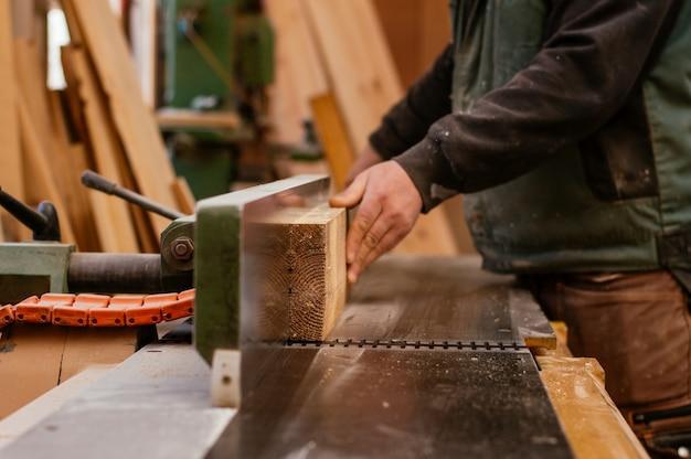Timmerman die een houten plank snijdt