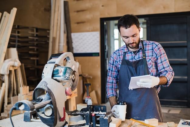 Timmerman die een koffiepauze met notitieboekje voor cirkelzaag in zijn atelier