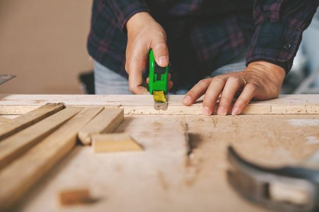 Timmerman die een meetlint op de werkbank houdt. bouwnijverheid, doe het zelf. houten werktafel.