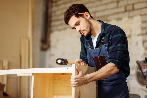 Timmerman die een spijker hamert in houten raad