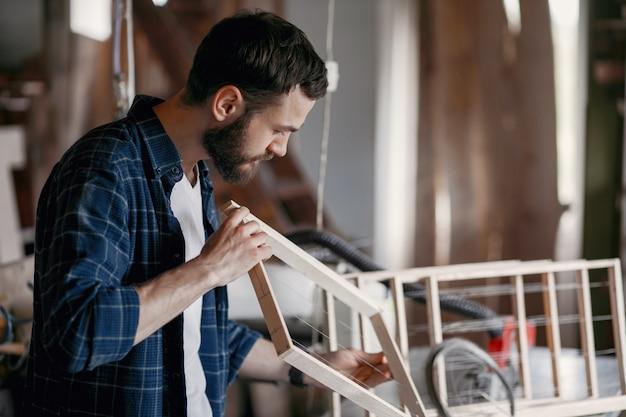 Timmerman die een spijker in een workshop hamert