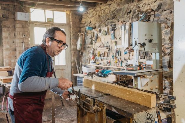 Timmerman die hout gebruikt om sculpturen te maken in het atelier
