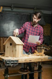 Timmerman die houten nestkast maakt
