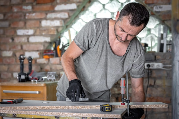 Timmerman die houtwerk doet met behulp van klemmend handgereedschap in zijn atelier.