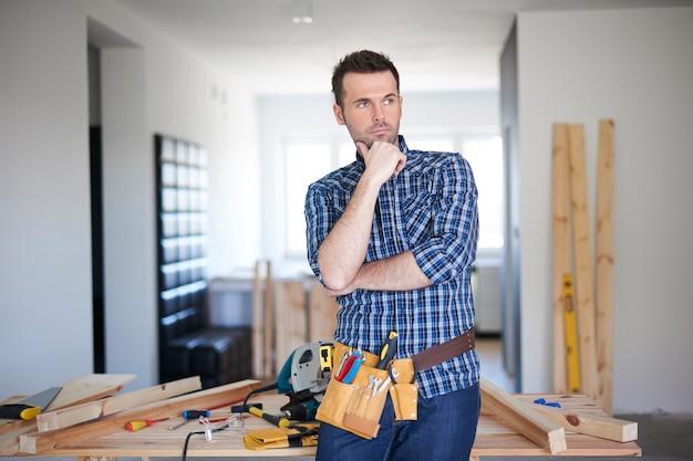 Timmerman die in een huis werkt en denkt