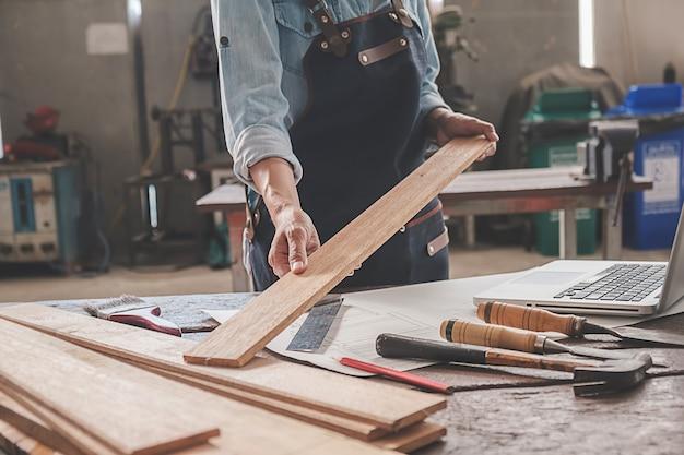 Timmerman die met apparatuur aan houten lijst in timmerwerkwinkel werken. vrouw werkt in een timmerwinkel.