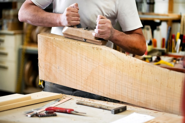 Timmerman die met een schaafmachine aan een blok van hout werkt dat de oppervlakte in dichte omhooggaand van zijn handen gladmaakt