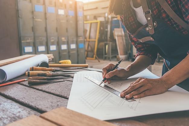 Timmerman die met materiaal aan houten lijst in timmerwerkwinkel werken
